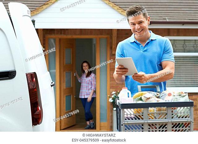Portrait Of Driver Delivering Online Grocery Order To House Using Digital Tablet