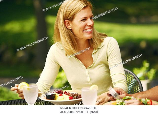 Close-up of a mid adult woman sitting at a table with a plate of salad in front of her