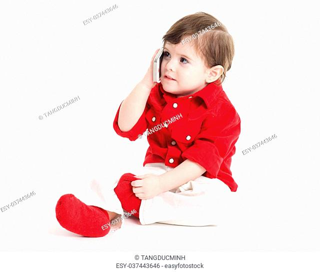 Toddler baby sitting and holding a mobile phone
