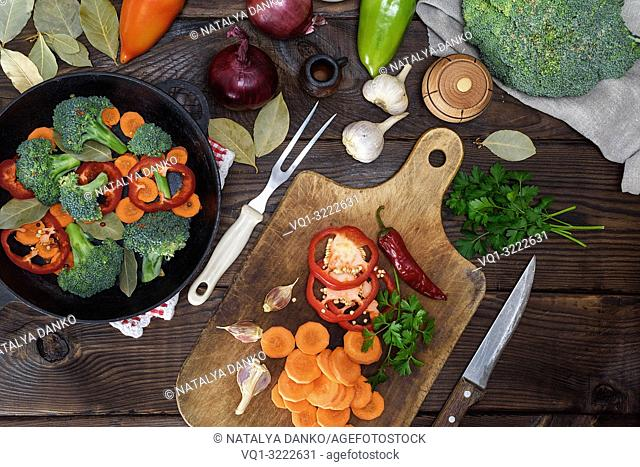 fresh pieces of carrots, broccoli and red pepper on a wooden kitchen board, next to a round cast-iron frying pan