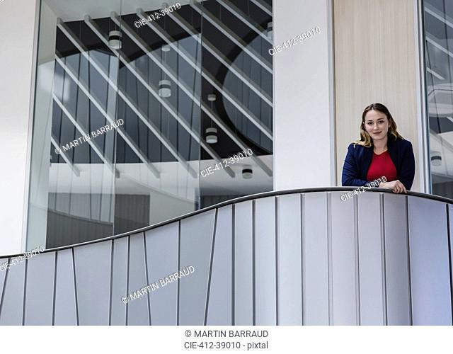 Portrait smiling, confident businesswoman standing on modern office balcony
