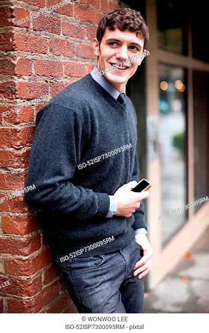 Businessman leaning against brick wall