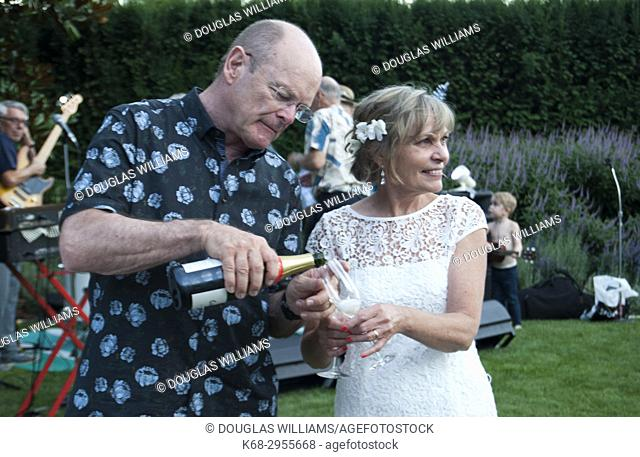 A man, 65, pours sparkling wine for a woman, 65, at an outdoor wedding in West Vancouver, BC, Canada