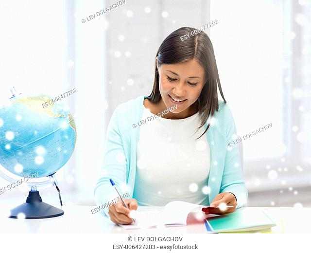 education, winter, technology and people concept - smiling young woman with globe and tablet pc computer indoors