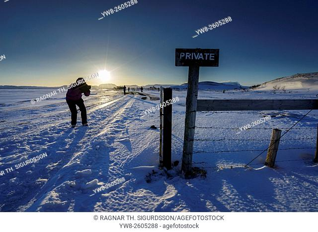 Person taking a picture in snowy landscape, Lake Myvatn area, Iceland