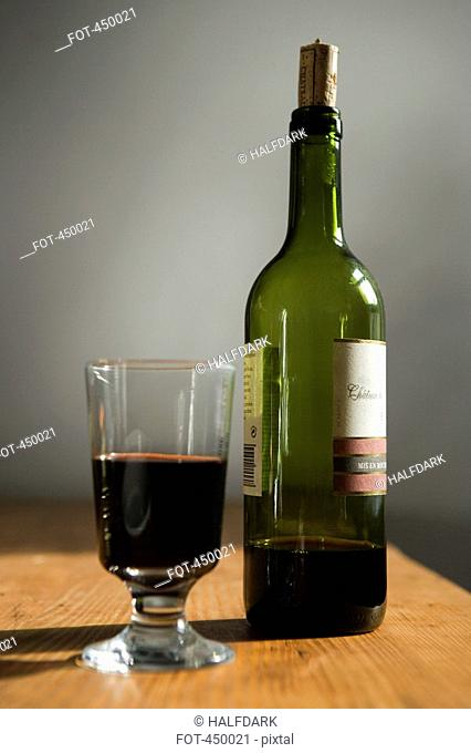 A bottle of red wine and a glass