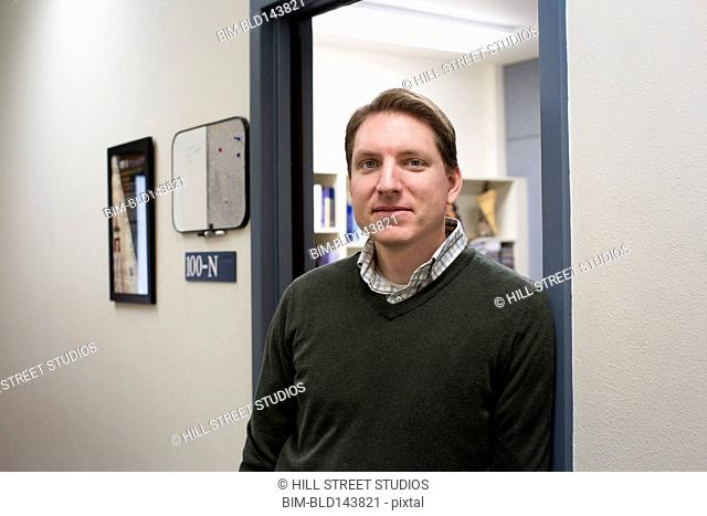 Caucasian college professor smiling at office doorway