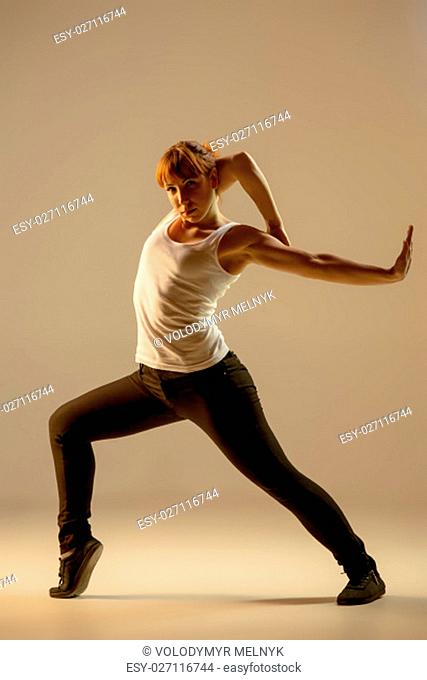 The women dancing fitness or hip hop choreography in beige studio background
