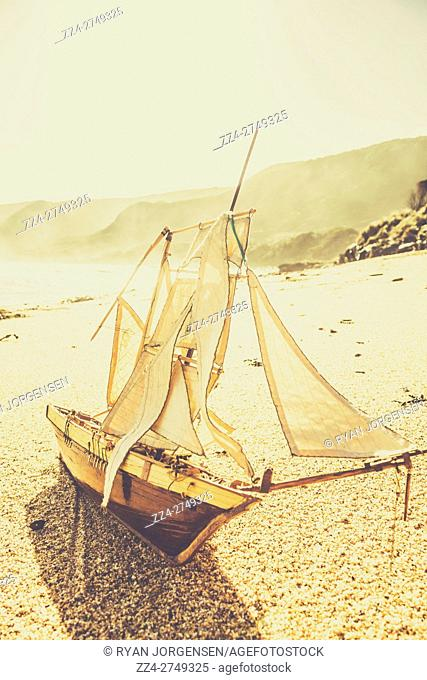 Classic martime sailing themed photo on a wood replica sailing boat docked on the shoreline of a pristime vintage beach. Taken Trial Harbour, Tasmania