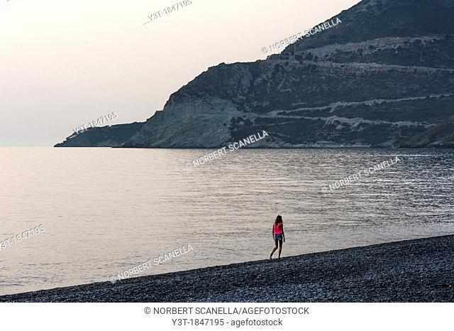 Europe, France, Corse, Haute Corse 2B, Cap Corse. Nonza. Young girl walking on the black pebbles beach