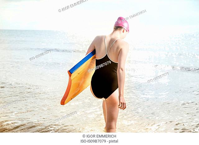 Young woman carrying surfboard in sea, Folkestone, UK