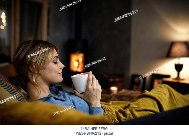 Smiling woman with cup of coffee relaxing on couch at home in the evening