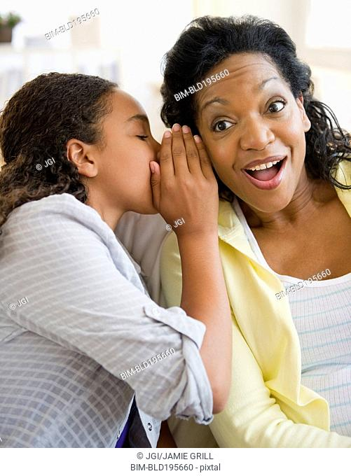 Daughter whispering secret to mother