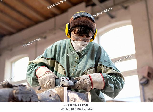 Art foundry, Female foundry worker polishing metal