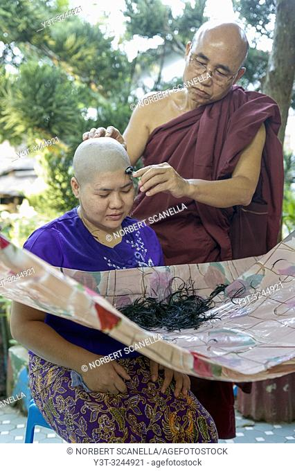 Myanmar (formerly Burma). Mon State. Mawlamyine (Moulmein). Gaungse Kyun, Shampoo island. Monk shaving the head of a young woman during her introduction