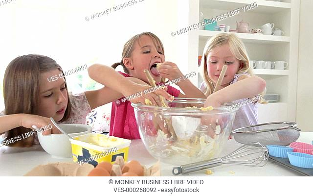 Three young girls adding ingredients into glass mixing bowl and tasting mixture.Shot on Canon 5D Mk2 at a frame rate of 25fps