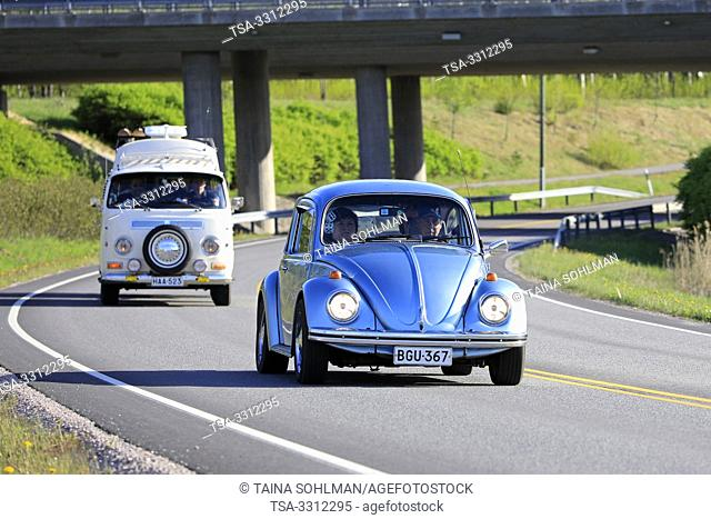 Salo, Finland. May 18, 2019. Classic 1970s Volkswagen Beetle, or Type 1 and white VW camper van, or Type 2 on road on Salon Maisema Cruising 2019