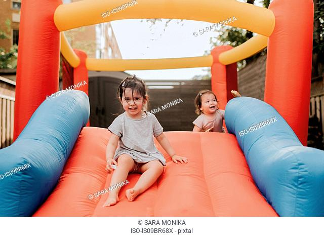 Sisters playing on inflatable slide