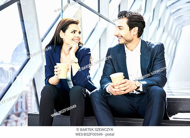 Smiling businesswoman and businessman having a coffee break in modern office