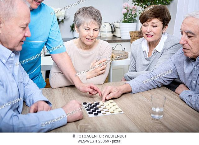 Nurse helping with a games evening for elderly people