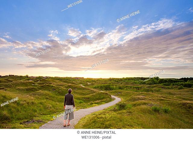 Woman walking on a trail that winds through the dunes on the island of Baltrum,just a trail for walking, for being in that landscape