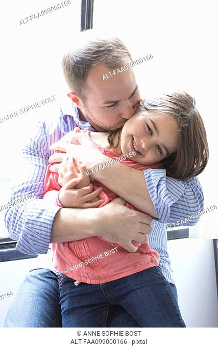 Father holding daughter on his lap, kissing her cheek