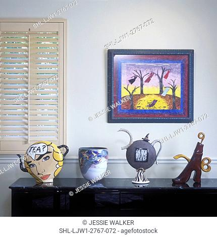 COLLECTION DISPLAYS - A buffet table with four very unique teapots, framed painting over table in Dining Room