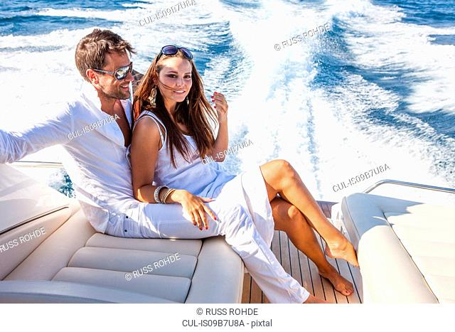 Portrait of couple relaxing on yacht, on water