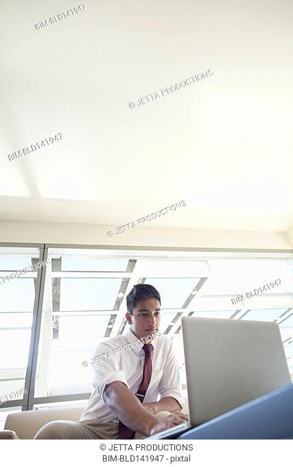 Low angle view of Indian businessman using laptop in office lobby