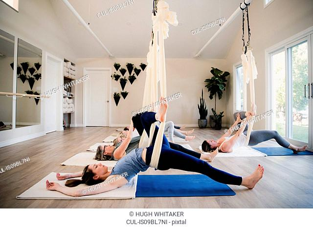 Women doing aerial yoga at retreat