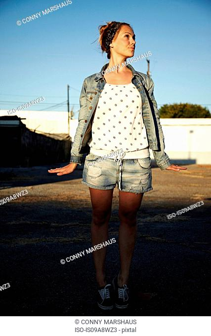 Woman standing in industrial area with hands to side