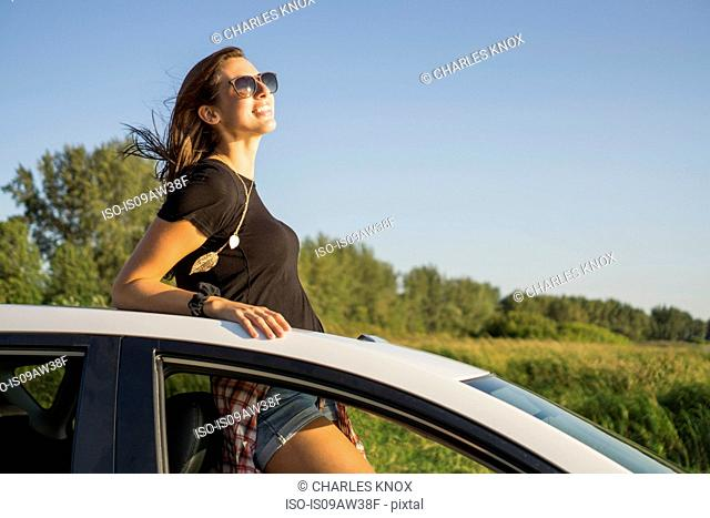 Young woman standing through sunroof enjoying view