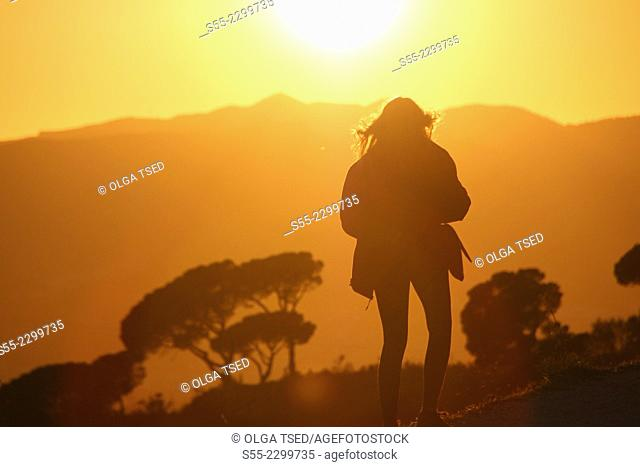 Young woman taking a picture of sunset, Passeig de les Aigües, Collserola mountain, Barcelona, Catalonia, Spain