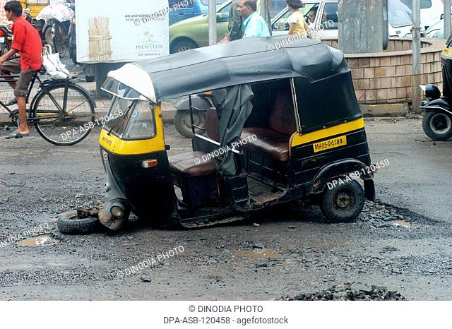 Auto rickshaw breaks down due to bad shape of road filled with pot holes causing traffic jams and accidents at Thane city near Bombay Mumbai; Maharashtra; India