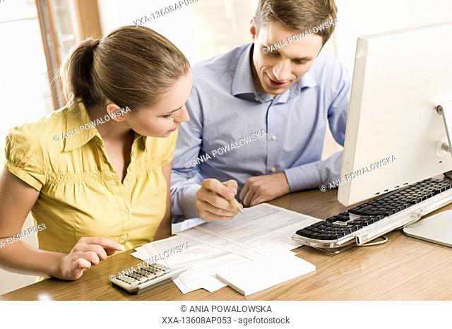 couple fill up tax return documents