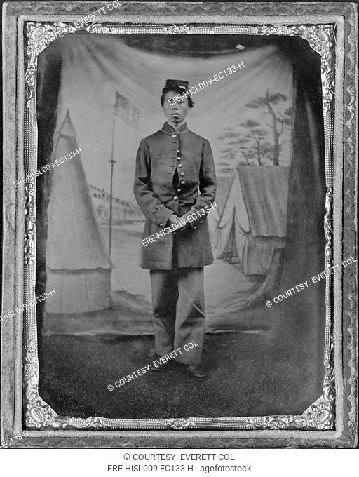 African American soldier posed in front of quaint studio backdrop of tents in a military camp with a prominent U.S. flag