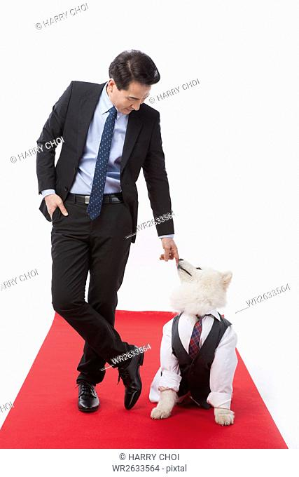 Middle aged businessman and his pet dog on red carpet