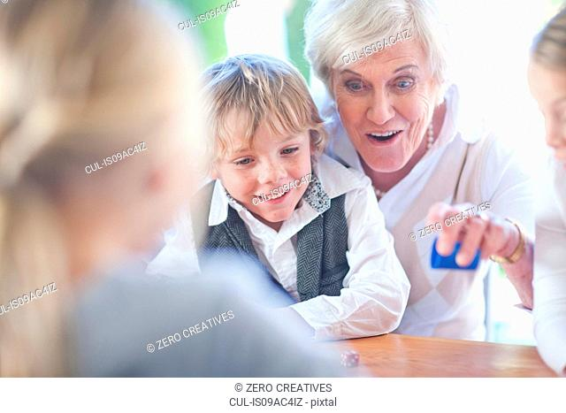 Senior female playing board game with grandchildren