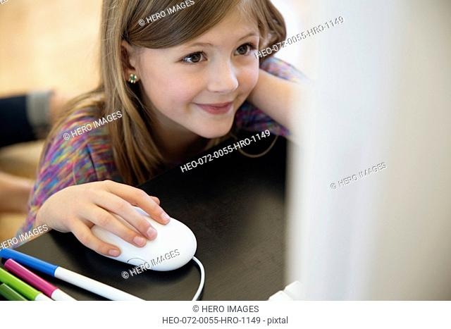 Little girl using computer mouse at table