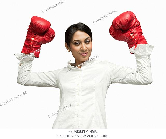 Businesswoman in boxing gloves cheering with arms raised