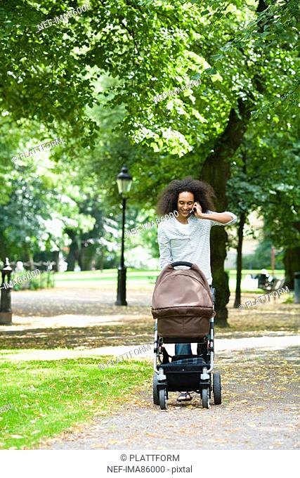 Young man pushing baby carriage in park and talking on mobile phone