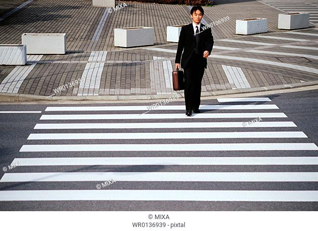 A man walking on zebra crossing