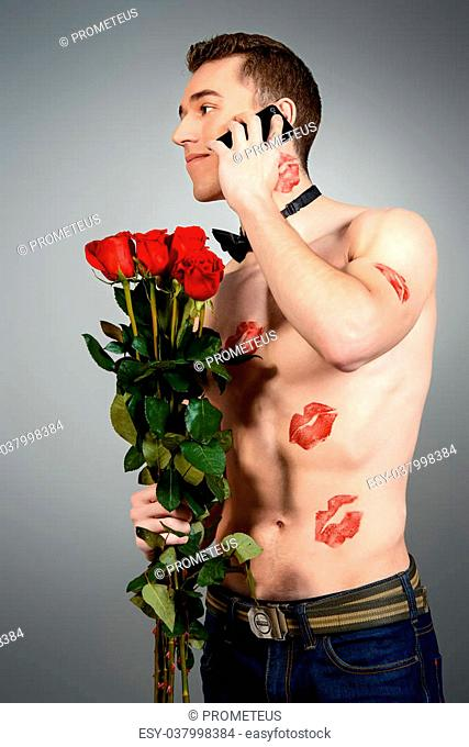 Sexual muscular young man shirtless holding a bouquet of red roses. He is covered with kisses. Love concept. Valentine's day