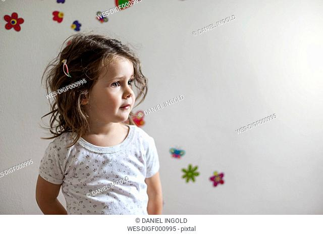 Girl standing in front of wall decorated with flowers