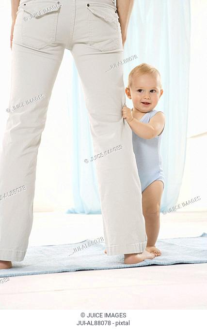 Baby holding on to mother's pants