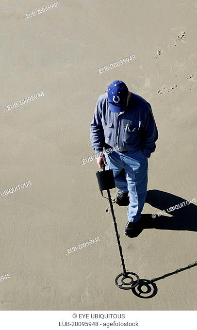 Man using a metal detector on the beach