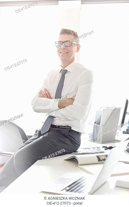 Portrait confident businessman with eyeglasses sitting on desk with arms crossed