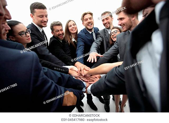 concept of team building. large group of business people standing with folded hands together