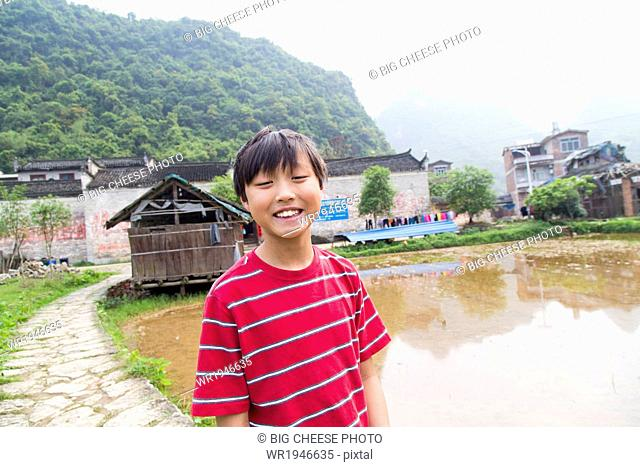 Smiling boy near a rice paddy in a rural village, Yangshuo, China