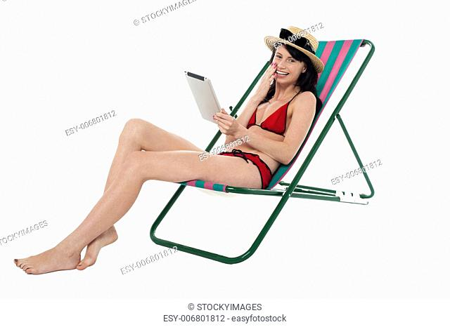 Sexy bikini woman relaxing and operating touch pad device